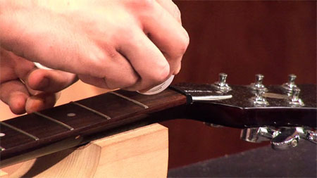 Dissolving glue on a guitar fretboard with Super Solvent CA glue debonder
